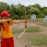 A MMA summer camper leaning archery