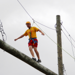 A MMA summer camper walks across a high ropes obstacle