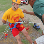 A summer camper rappeling from a 30ft tower.