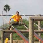 A camper slides down two poles on the combination obstacle